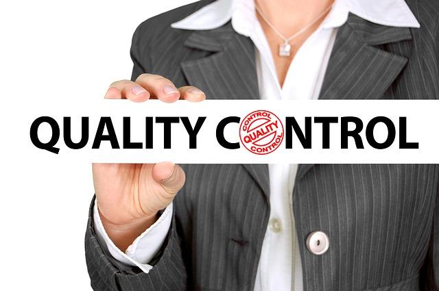 Žena v sivom saku drží v rukách ceduľku s nápisom kontrola kvality.jpg